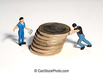 Moving The Euro - Two miniature workmen figurines moving a...