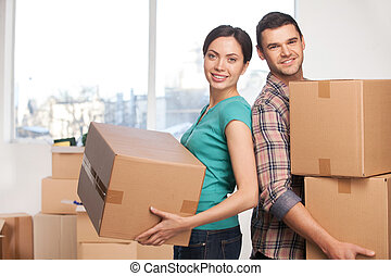 Moving to a new apartment. Beautiful young couple standing...