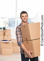 Moving to a new place. Cheerful young man holding a cardboard box and smiling at camera while more carton boxes laying on background
