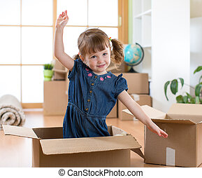 Moving to new apartment. Happy child in cardboard box.