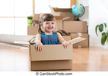 Moving to new apartment. Happy kid in cardboard box.