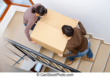 Moving to new home - Two young women carrying up cardboard...