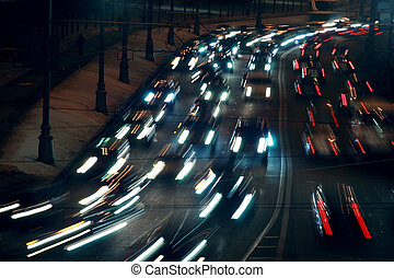 moving traffic at night with moving lights at winter; many cars