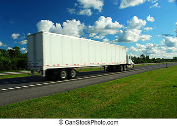 Moving truck - Fast moving eighteen wheeler on a highway, ...