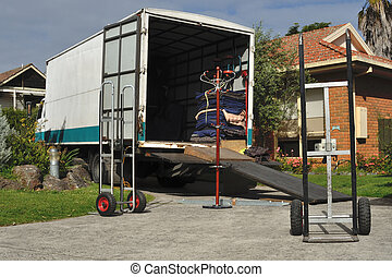 Moving truck loaded with furniture, trolleys, ramp and ...