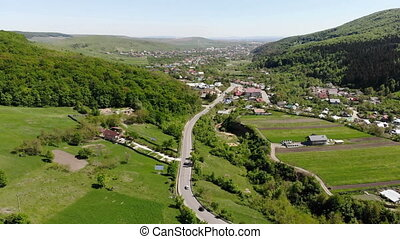 Moving up drone above mountain village road - Aerial view of...