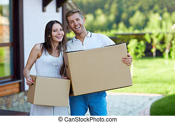 Young couple with boxes by the house
