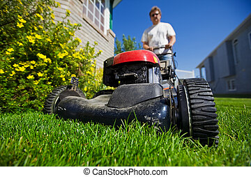 Mow the lawn - A man mowing the front lawn with focus on the...