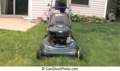 Mowing Grass 1 - Moving with lawn mower on the grass. Shot...