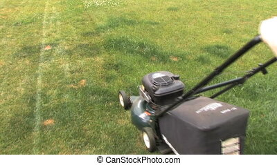Mowing Grass 2 - Moving with lawn mower on the grass. Shot...
