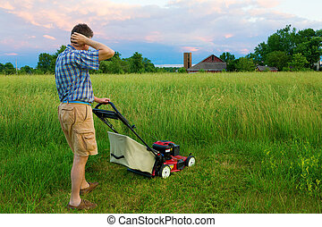 Man is tasked to mow a field of tall grass