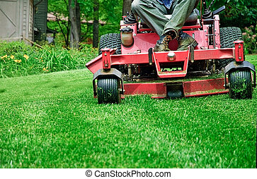 Closeup of a man on a riding lawnmower.