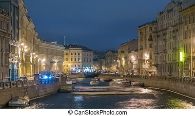 Moyka river timelapse in Saint Petersburg, Russia at night with a motion blurred touristic boat, illuminated old buildings.