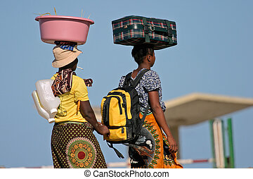 Mozambican woman in traditional dresses carrying their luggage on their heads