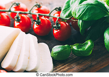 Mozzarella, cherry tomatoes and basil leaves on wooden cutting board