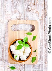 mozzarella in a wooden bowl with basil