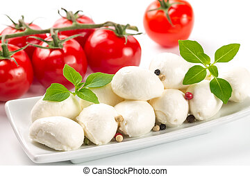 Mozzarella, tomatoes and fresh basil leaves on white background