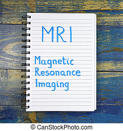 MRI- Magnetic Resonance Imaging text written in notebook on wooden background