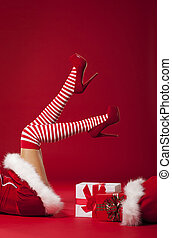 Mrs santa claus legs in striped stockings with christmas...