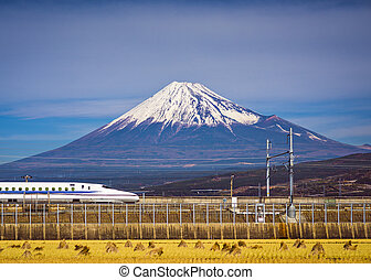 Mt. Fuji in Japan with a train passing below.
