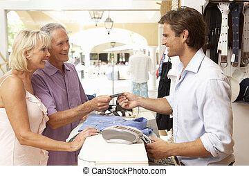 mužský, draba assistant, v, pokladna, o, šatstvo nadbytek, s, zákazník