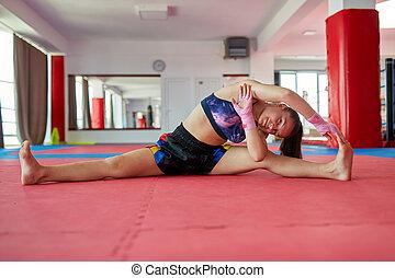 Muay thai girl stretching - Muay thai female fighter...