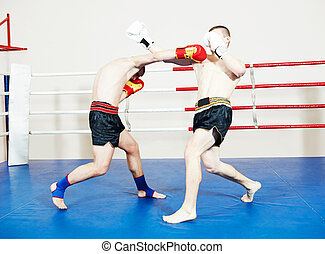 Muay thai sportsman fighting at boxing ring