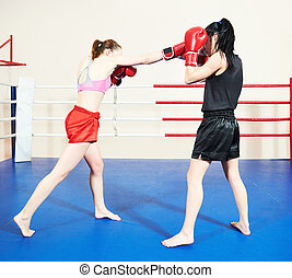 Muay thai woman fighting at training ring