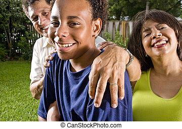 muchacho adolescente, con, padres orgullosos