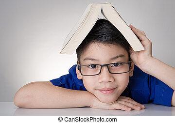 muchacho asiático, con, libro, en, cabeza, pensamiento