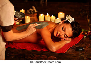 Mud mask of woman in spa salon. Back clay massage .