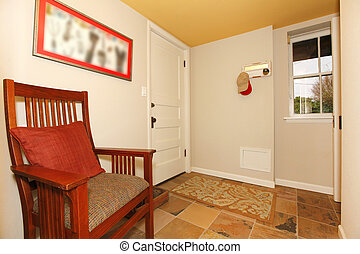 Mud room in the basement with nice chair.