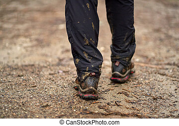 Muddy boots on mountain trail