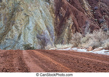 muddy canyon dirt road with rocky cliffs