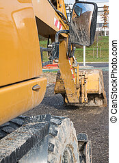 Muddy excavator shovel with rear-view mirror at construction are