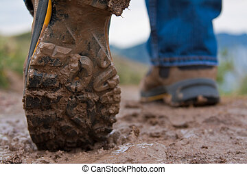 Close up of a man's boots while walking a muddy trail.