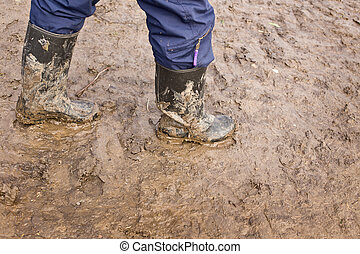 Human legs walking with muddy rubber boots on wet silt