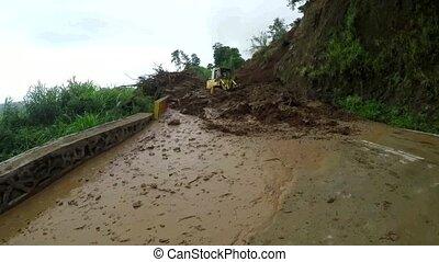 Mudslide debris being pushed by bulldozer on mountain road...