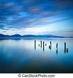 muelle de madera, o, embarcadero, restos, en, un, lago azul, ocaso, y, cielo, reflexión, en, water., versilia, toscana, italia