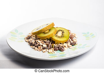 Muesli cereals bowl and spoon with almond, pine nuts, walnut, raisins, oat and wheat flakes, sultanas, fresh fruits kiwi, strawberry pieces, banana, pomegranate seeds