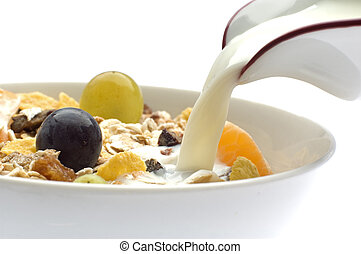 muesli - milk pouring in a bowl of muesli with grapes