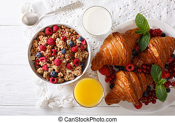 Muesli with berries and croissants, milk and orange juice close-up on the table. horizontal top view