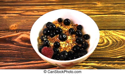 Muesli with berries falling into a porcelain bowl, Slow...
