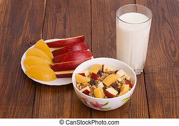 muesli with peach, apple and a glass of milk