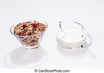 Muesli with red fruits and milk in glass isolated