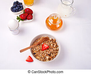 Muesli with strawberries, honey, milk on the white table. Flat lay.