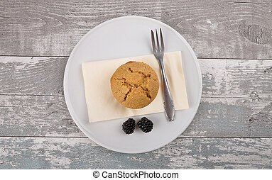 Muffin on plate and weathered wood