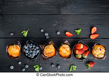 Muffin with blueberries, on black wooden table background, top view flat lay with copy space for text