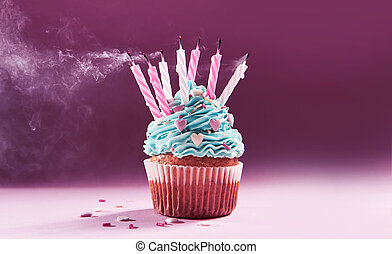 muffin with cream and extinguished candle. the concept of...