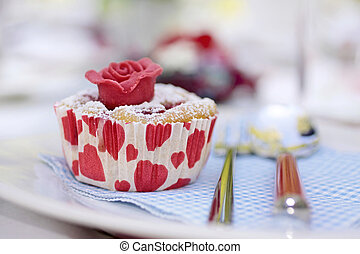 Muffin with marchpane rose on coffee table
